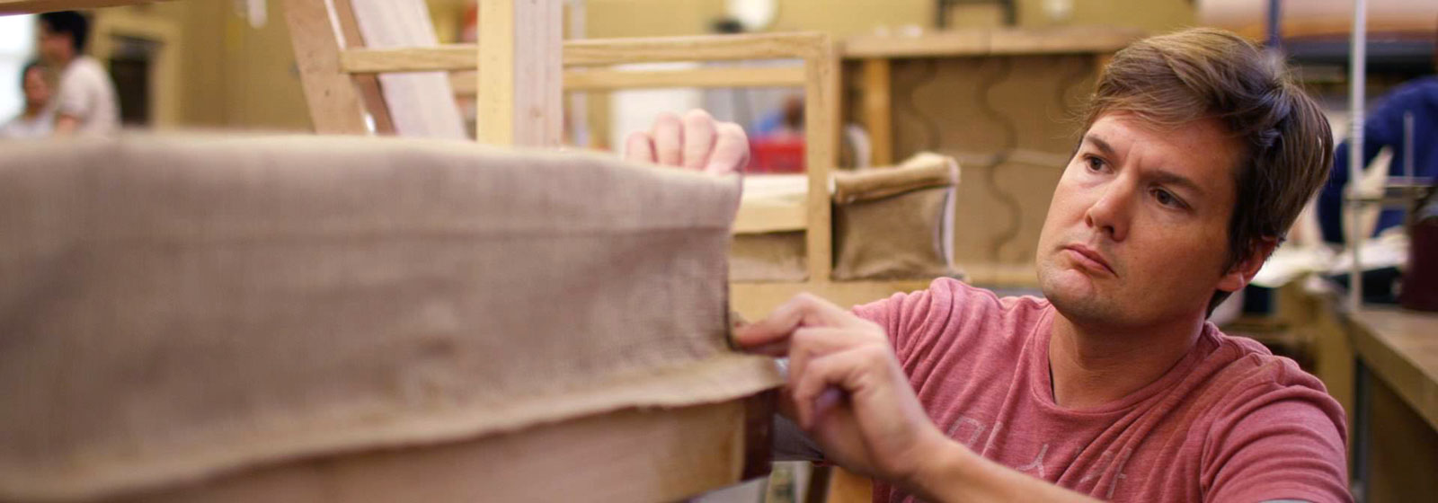 Student examining upholstery on chair