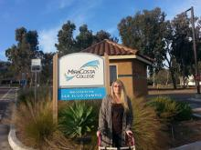 student Kimber Thurman in front of Mira Costa campus sign